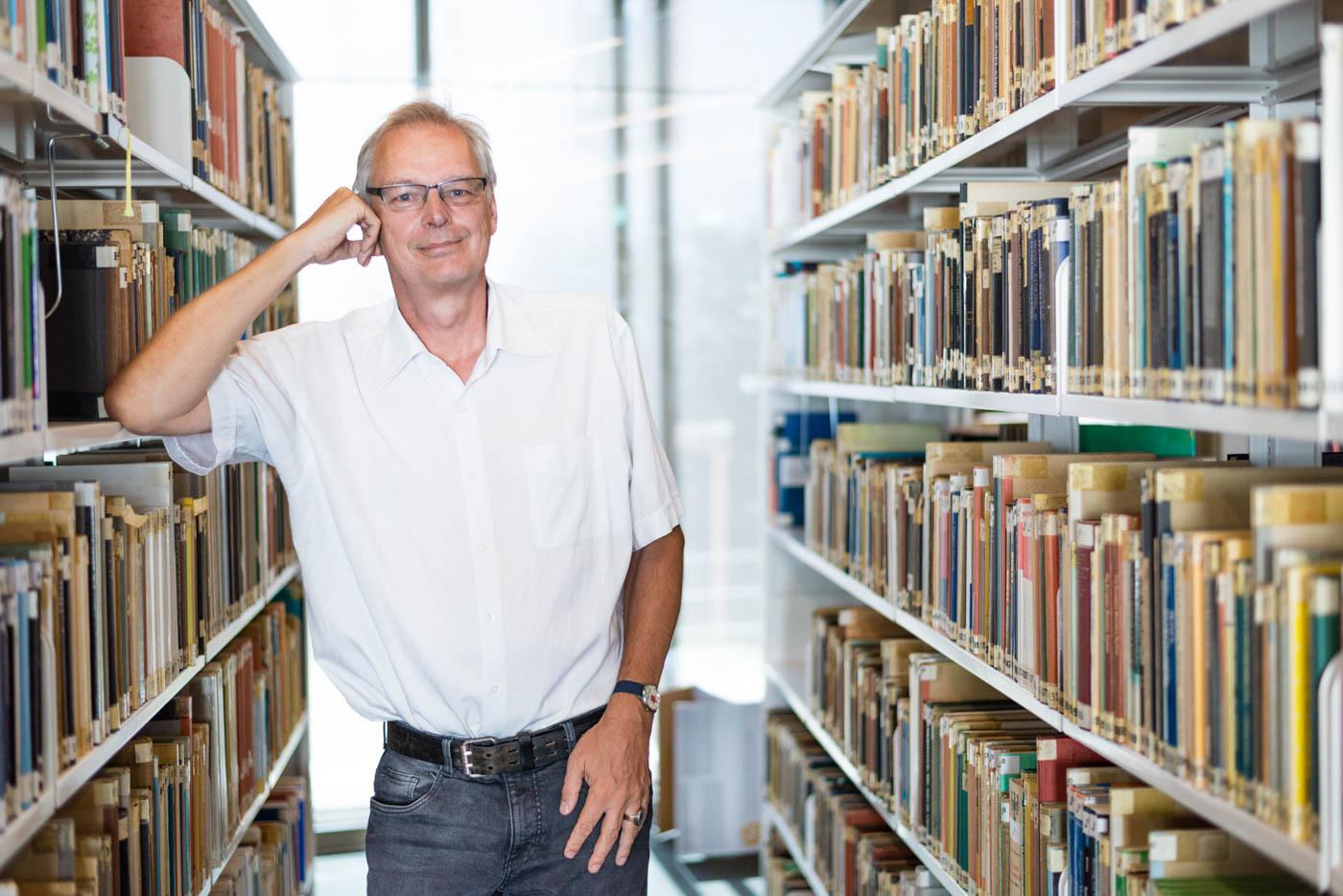 Herr Neumärker lehnt an Buchregal und lächelt