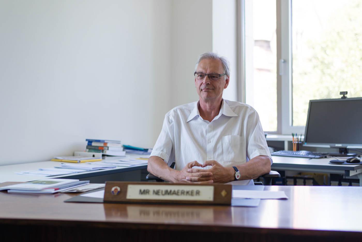 Herr Neumärker sitzt an Schreibtisch