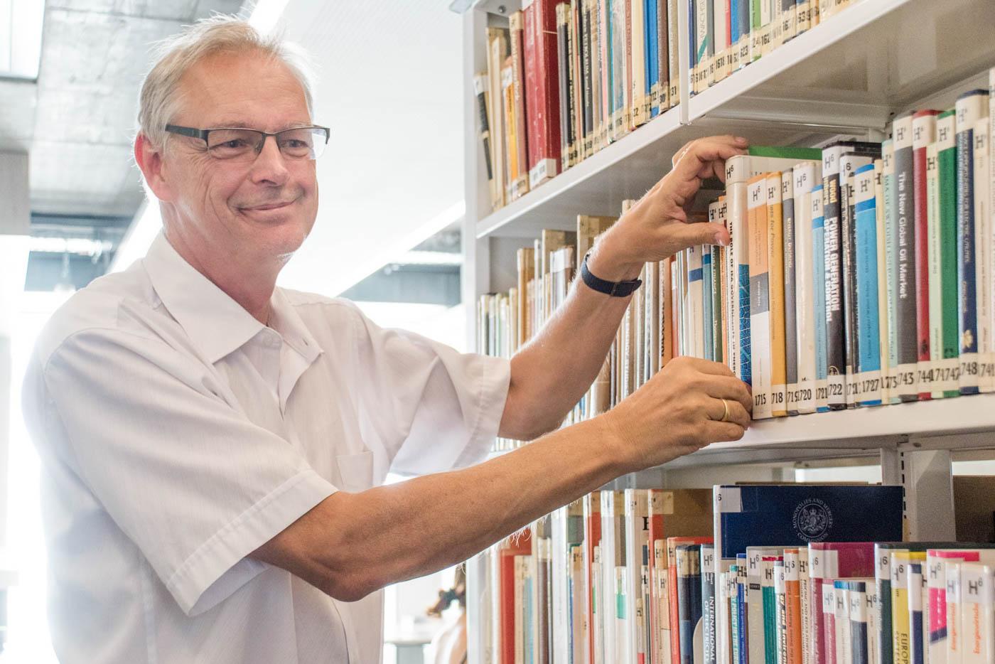 Herr Neumärker sucht Buch aus Regal
