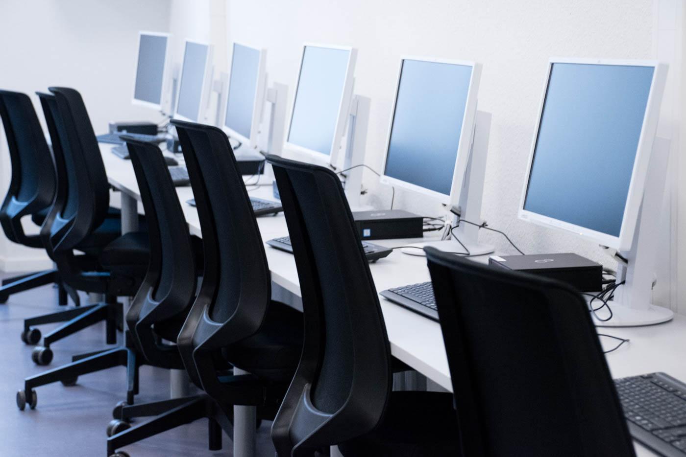 Stuhlreihe mit sechs Bildschirmen