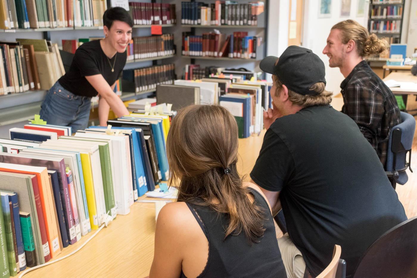 Samira erklärt drei Studierenden etwas