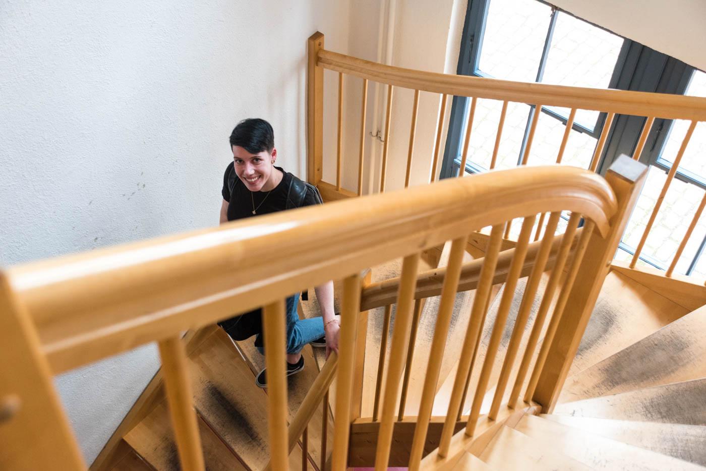 Samira geht Treppe im Institutsgebäude herunter
