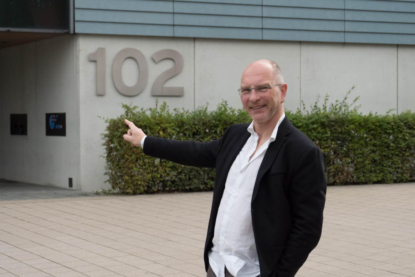 Herr Stieglitz weist auf Gebäude 102