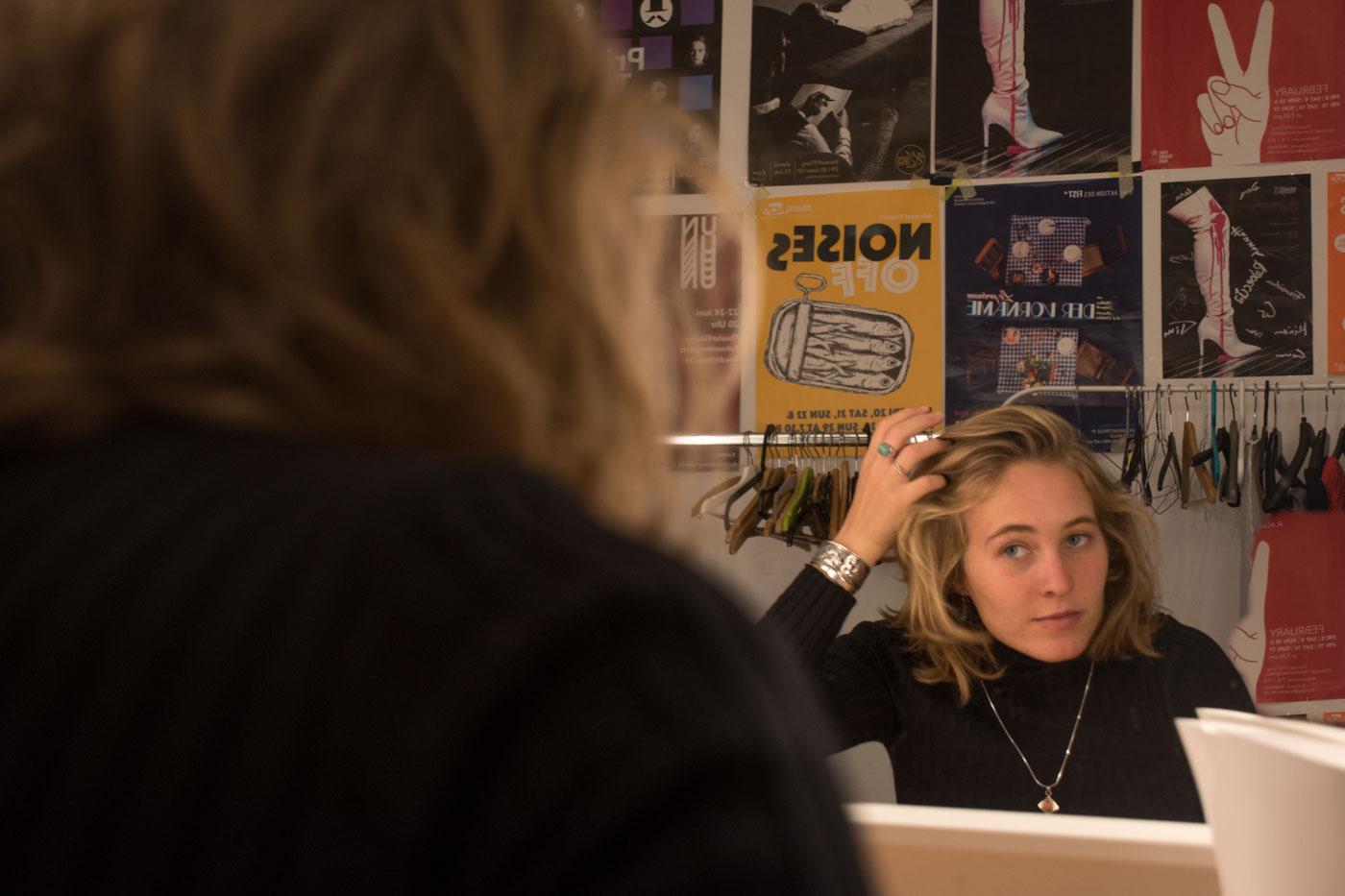 Daniela vor Spiegel, macht sich die Haare.