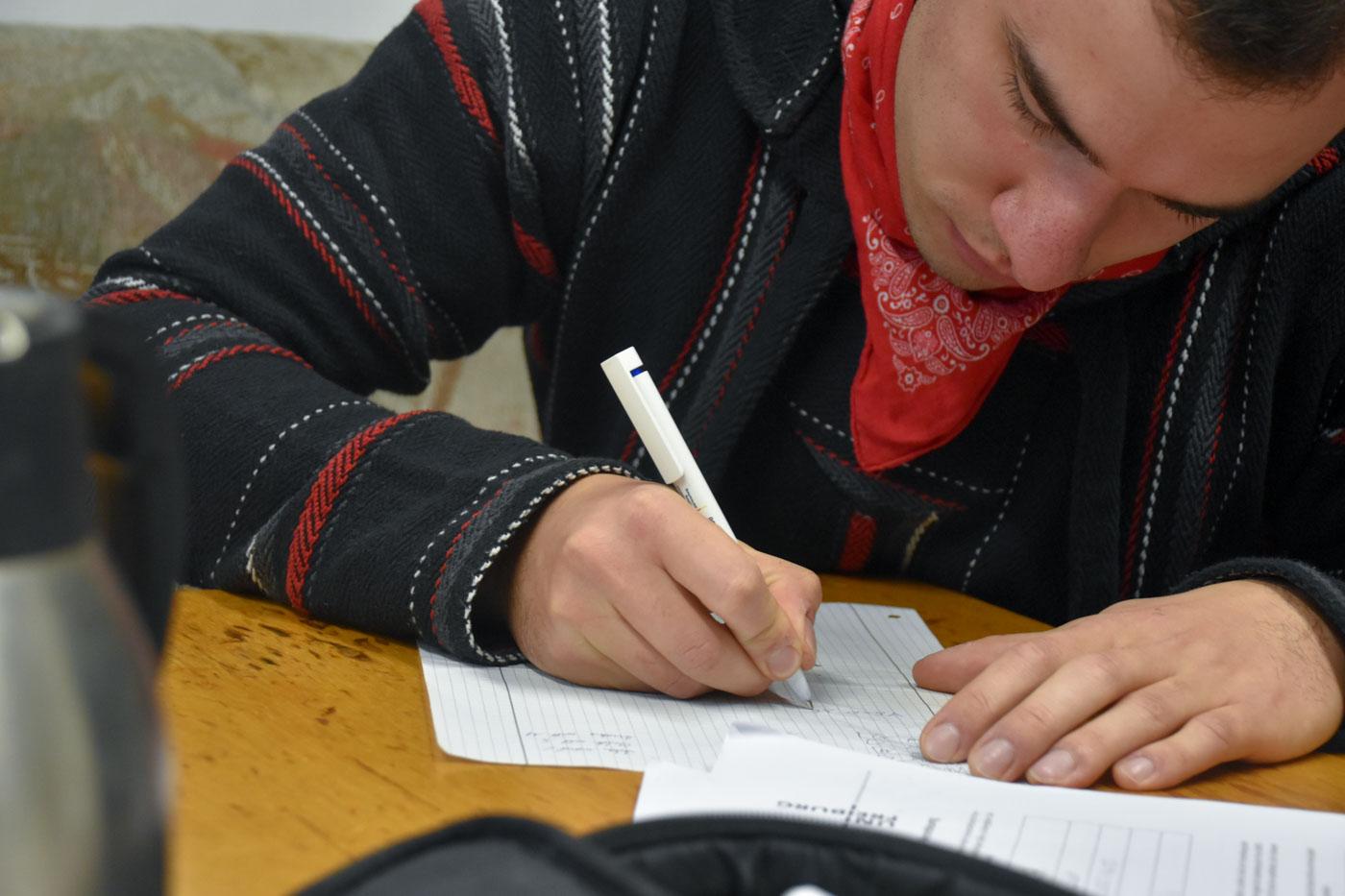 Max schreibt Matheaufgabe auf Papier