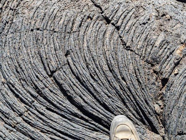 Mit einem halben Fuß auf Pahoehoe-Lava (El Hierro, Kanarische Inseln, Spanien).