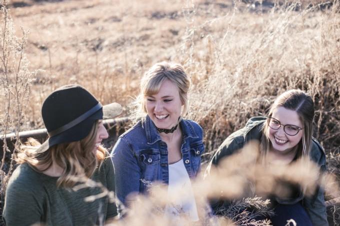 Drei junge Frauen unterhalten sich lachend - in der Natur sitzend